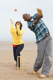 Young Couple Playing Cricket On Beach Holiday Stock Images