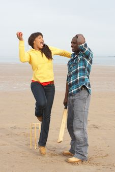 Young Couple Playing Cricket On Beach Holiday Royalty Free Stock Photos