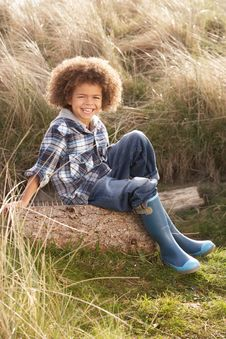 Free Young Boy Putting On Wellington Boots Stock Photography - 15687612