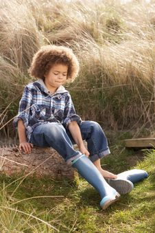 Free Young Boy Putting On Wellington Boots Royalty Free Stock Photos - 15687618