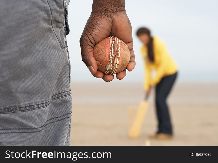 Young Couple Playing Cricket On Autumn Beach Holid