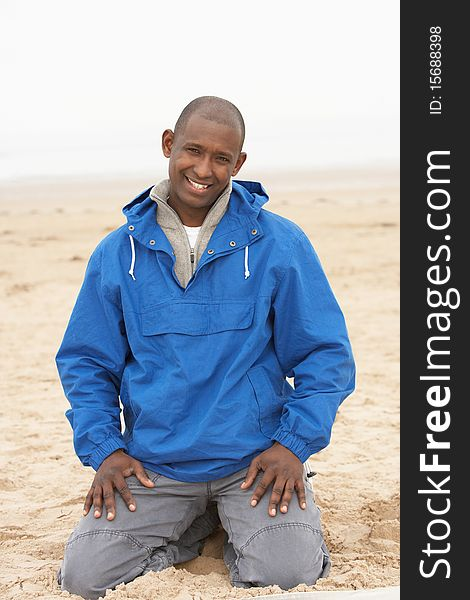 Man Relaxing On Beach In Autumn Clothing