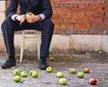 Free Businessman Cleaning Apples Sitting On A Stool Royalty Free Stock Images - 15691929