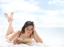 A Young And Sexy Brunette Is Reading A Book Stock Photos