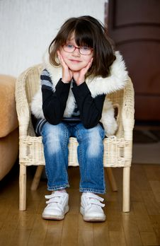 Nice Toddler Girl  In Glasses Siiting On Chair