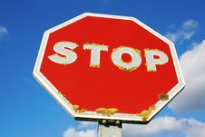 Old Red STOP Sign Over Blue Sky Background Stock Photo