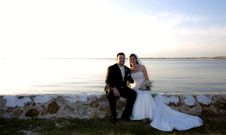 Free Wedding Couple Sitting By Water Royalty Free Stock Photos - 15765588