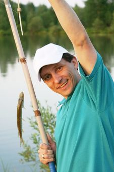 Smiling Fisherman With A Rod And A Fish Royalty Free Stock Image