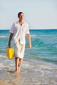 Free Man With Yellow Suitcase Walking On Beach Stock Images - 15790404