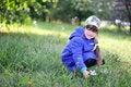 Free Nice Little Girl In Blue Coat Picks Up Flowers Stock Photo - 15835360
