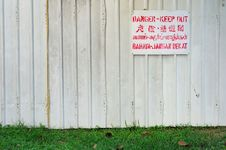 Danger Signboard On White Fence Stock Photo