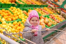 Little Girl With A Basket In Shop Royalty Free Stock Photos