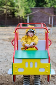 Small Girl In Yellow Rain Coat In Playground Car Royalty Free Stock Image