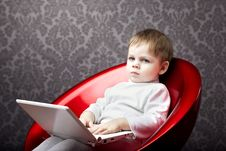 Free Boy Sitting In A Chair With A Laptop Stock Photo - 15904770