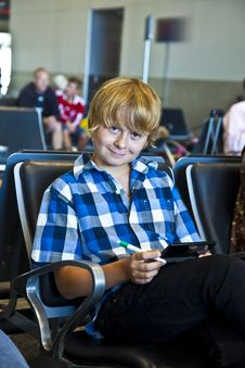 Boy Is Waiting For Departure At The Airport Royalty Free Stock Image