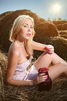 Free Woman Sitting On The Hay And Eat Raspberries Royalty Free Stock Photos - 15921588