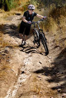 Young Woman Mountain Biking Stock Photo