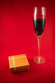 Free Glass Wineglass, Red Wine And Gift Box On Red Back Royalty Free Stock Photography - 15945647