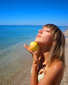 Free Beautiful Young Woman With Apple On Seashore Royalty Free Stock Photography - 15984377