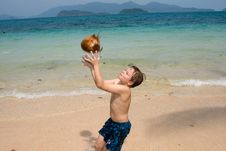 Boy Is Playing With A Coconut On A Beach Stock Photography
