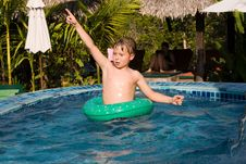 Free Young Boy In A Floting Tyre Enjoys The Pool Royalty Free Stock Photos - 15990428