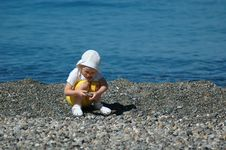 Small Child Sits On Seaside Royalty Free Stock Images