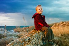 Free The Little Boy Sitting Against The Sea Royalty Free Stock Photography - 16016637