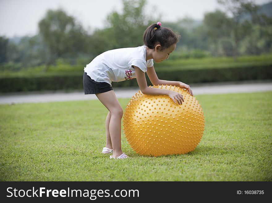 Asian girl play ball in the grass
