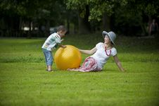 Mother And Son In Grass And Play Ball
