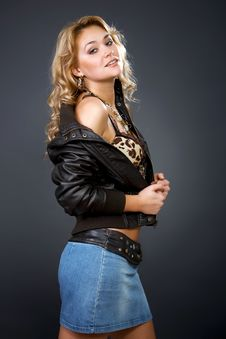 Sexy Woman In A Leather Jacket And Jeans Skirt Stock Image