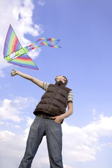 Man Playing With Multicolored Kite Royalty Free Stock Images