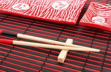 Sushi Plates And Chopsticks On Bamboo Mat Royalty Free Stock Image