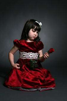 Free Cute Girl In Red Holiday Dress Looking At Rose Royalty Free Stock Photography - 16147047