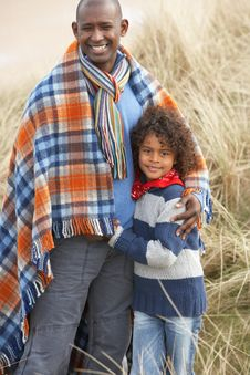 Father And Son Wrapped In Blanket Amongst Dunes On Royalty Free Stock Photo