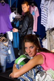 Free Smiling Girl In Dress Store. She Lays On Shirts. Royalty Free Stock Image - 16226316