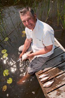 Free Senior Man Scaling Fish Stock Photography - 16228802