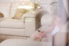 Free Young Girl Sitting In A Sofa And Using Phone Royalty Free Stock Images - 16238959