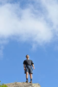 A Young Man Stands On A Cliff Top, And Seriously Royalty Free Stock Photos