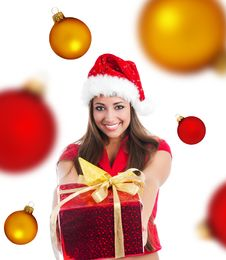 Cute Girl With A Xmas Gift And Spheres Royalty Free Stock Photos