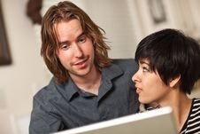 Happy Young Man And Woman Using Laptop Together Stock Photos
