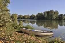 Boat On The Lake Bank In Autumn Stock Image