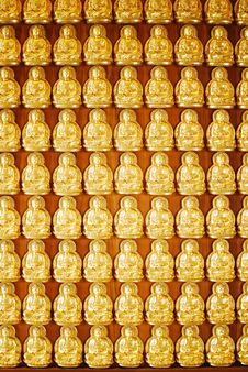 Many Of Golden Buddha Statue On Wooden Wall Stock Image