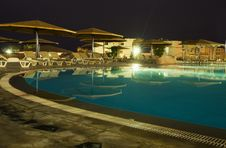 Night Picture Of Rest. Swimming-pool, Parasols And Sunbeds. Royalty Free Stock Photo