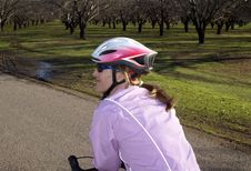 Female Cyclist In Almond Orchard Stock Image