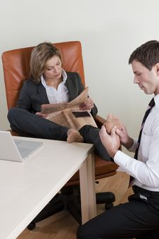 Free Female Manager Receiving Feet Massage Royalty Free Stock Images - 16337549