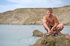 Free Smiling Young Man Is Squatting On The Rock Royalty Free Stock Image - 16340716