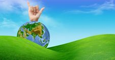 A Hand With A Globe And A Grass Field Stock Photo