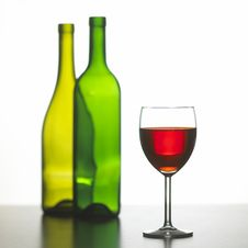 Glass Of Red Wine With Two Green Wine Bottles Stock Photography
