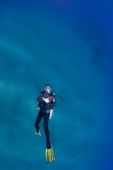 Female Scuba Swimming On Her Back Stock Photo