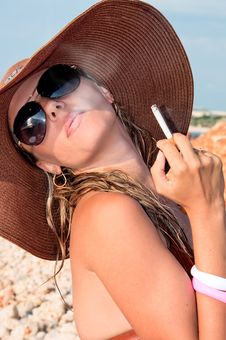 Attractive Woman In A Hat Smoking A Cigarette Royalty Free Stock Image